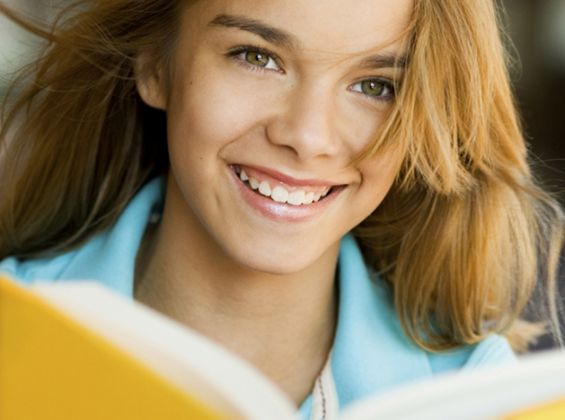 Young girl smiling reading book