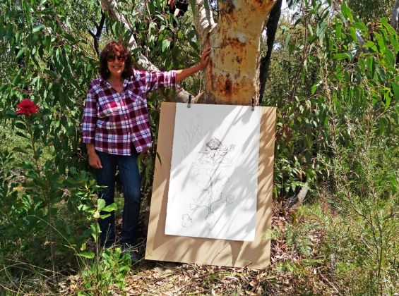 Photo of Yvette Pritchard with her drawing in the bush
