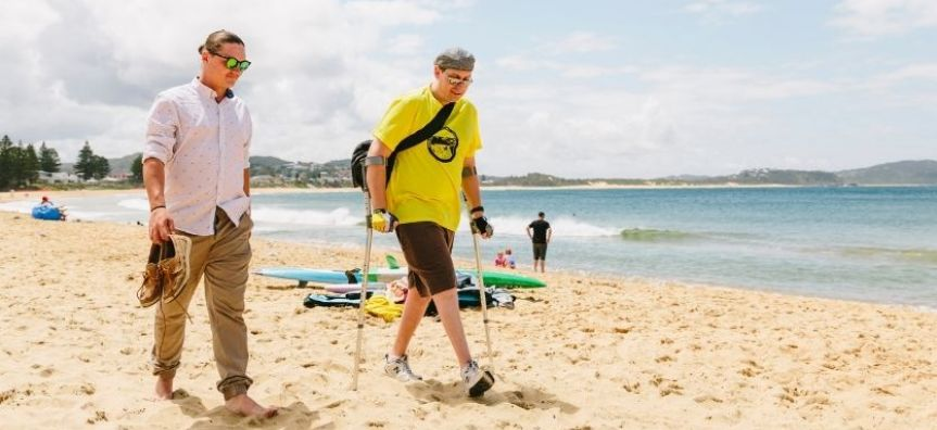 Two men walking on the sand at Terrigal beach. One is wearing a white button up shirt, brown trousers and sunglasses. He is barefoot. The other is wearing a yellow t-shirt and grey shorts, he is wearing a bag, hat and sunglasses and is holding crutches.