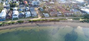 Aerial view of water with rock seawall and homes on lnd