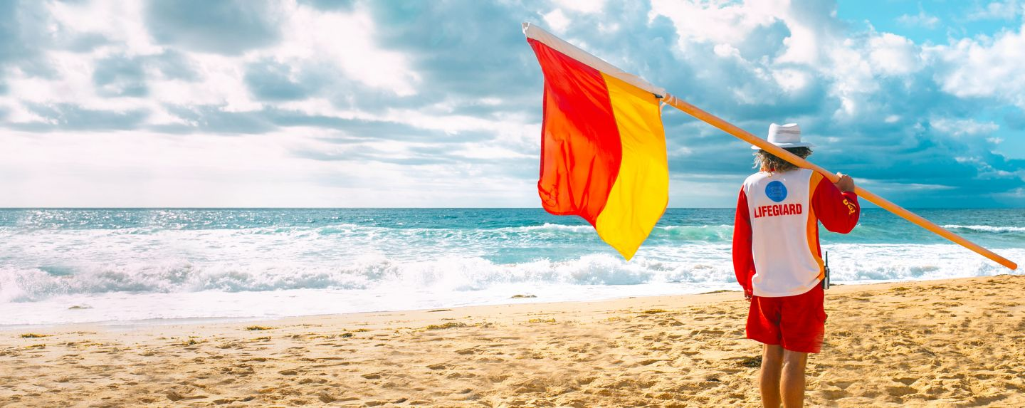 Lifeguard standing on beach with flag